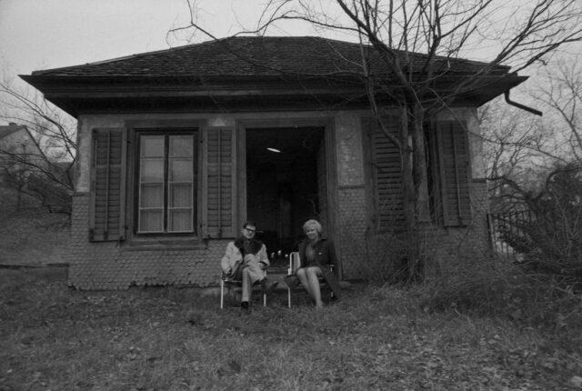 Schriftsteller Hermann Burger und Anne Marie Carell sitzen vor Burgers Gartenhaus