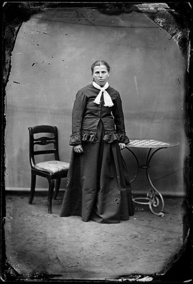 Giovane donna in piedi con sedia e tavolino per scacchi