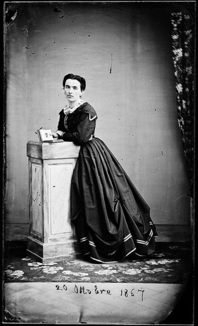 Maria Monotti Maestretti appoggiata a una colonna, con libro