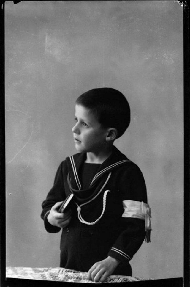 Bambino con fascia bianca al braccio sinistro