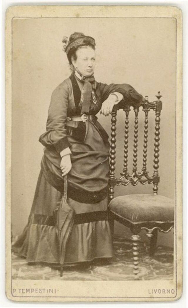 Donna in abito elegante appoggiata a poltrona, con ombrello