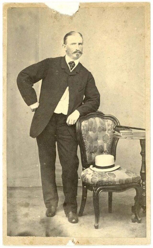 Uomo con pizzo accanto a poltrona e cappello