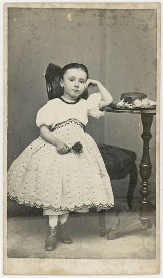 Bambina appoggiata a un tavolino