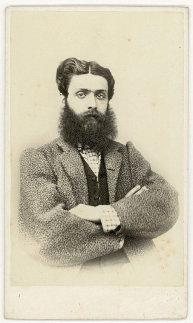 Giovane uomo con folta barba e pastrano