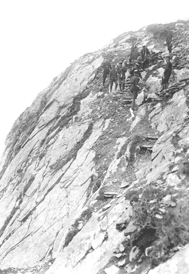 Die Tragbahre wird in steilem Gelände vorne geschultert und hinten getragen