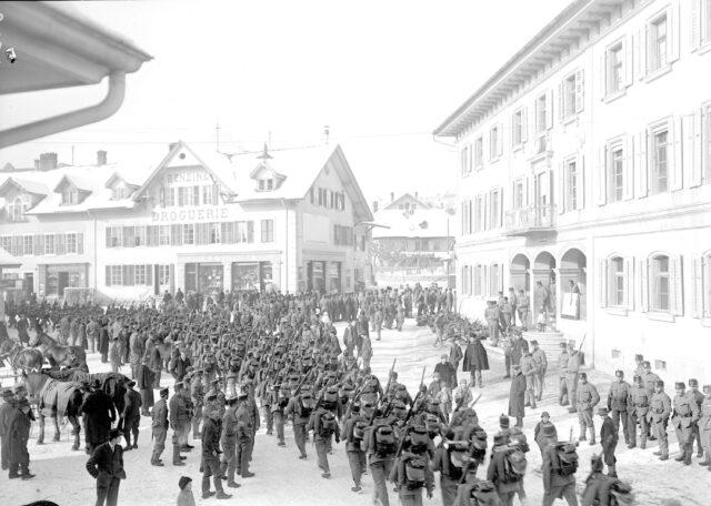 Fertig ausgerüstete Soldaten marschieren durch Tavannes