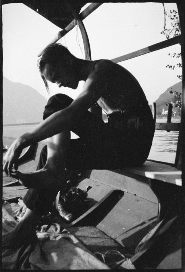 Josef Tcherv, se tenant le pied, dans une barque sur le lac de Lugano