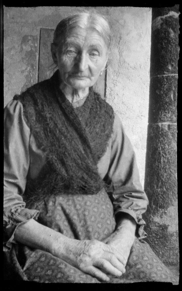 Femme âgée assise devant un mur à Bissone