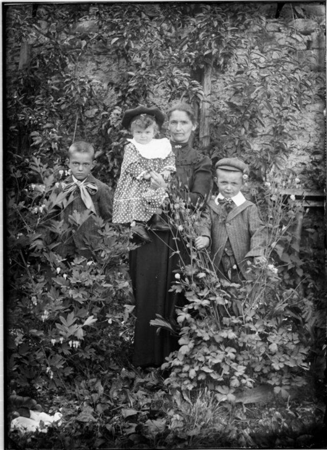 Madre con tre bambini in un giardino