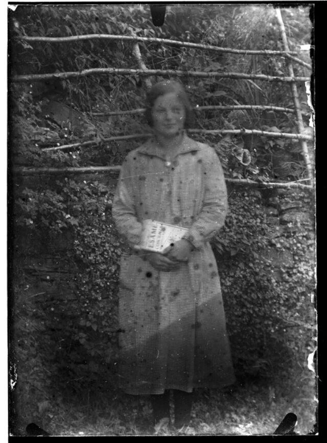 Ragazza in piedi davanti a una staccionata in legno con un libro tra le mani