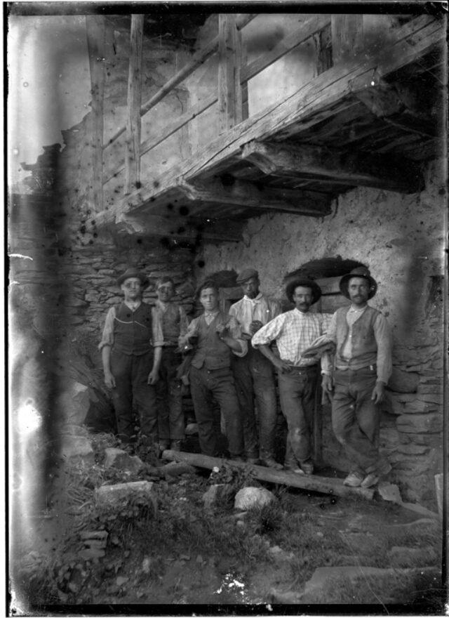 Gruppo di uomini in piedi davanti a una casa
