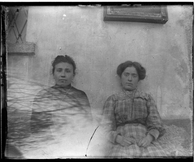 Due donne sedute contro il muro di una casa