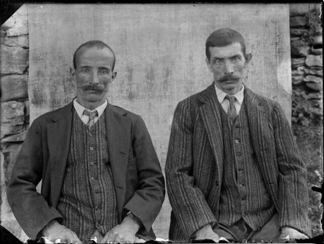 Giulio e Carlo Cizzio seduti davanti a un fondale appeso a un muro