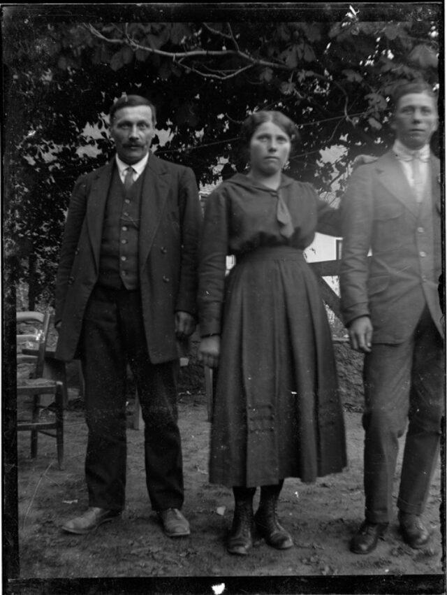 Una donna fra due uomini in piedi in giardino