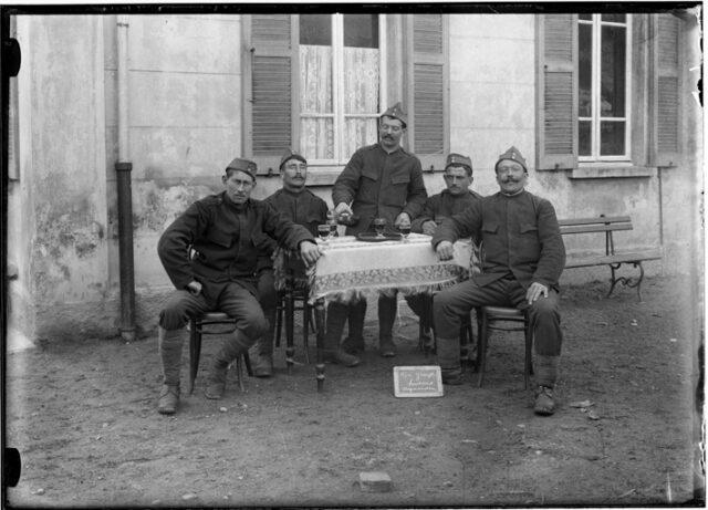 Ritratto di militari che bevono seduti ad un tavolo