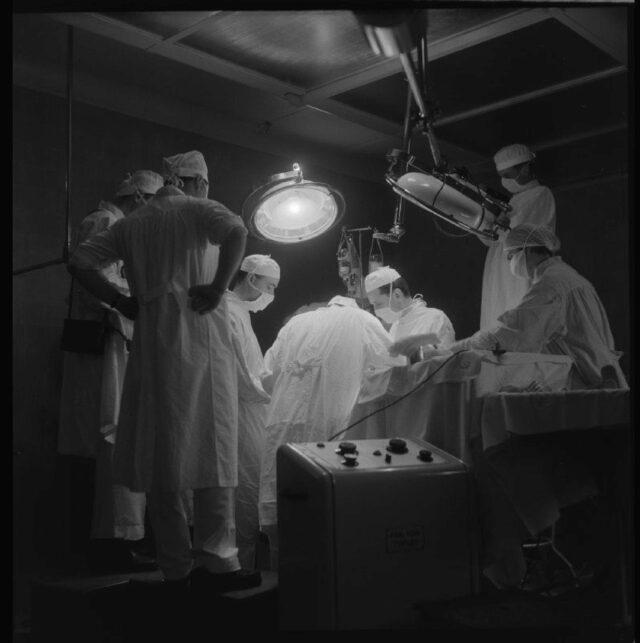 [Übersichtsaufnahme vom Operationssaal mit Chirurgen und Assistenten bei der Arbeit]