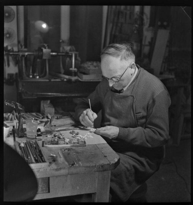 [Blick auf Handwerker in seiner Werkstatt sitzend am Schnitzen]
