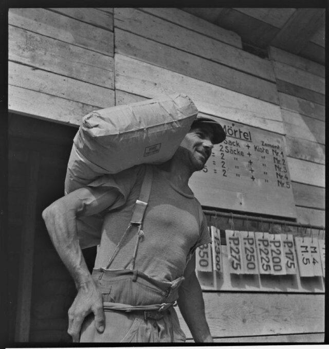 [Bauarbeiter trägt Mörtelsack auf der Schulter]