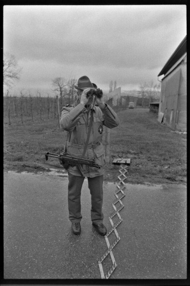 [Grenzwächter in Bardonnet-Genf mit einem Maschinengewehr schaut durch einen Feldstecher ]