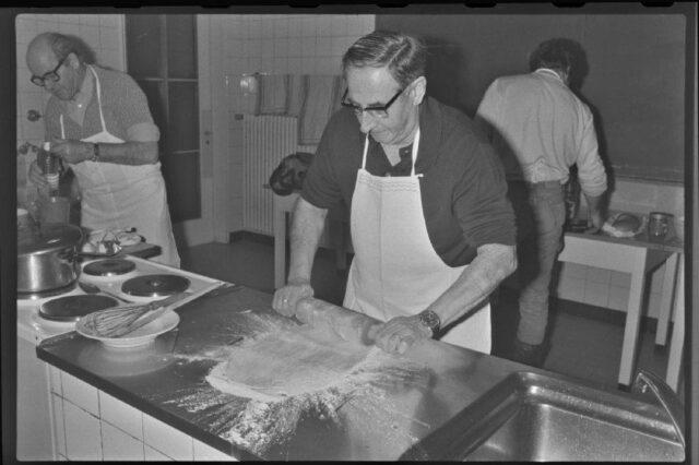 [Die Kursteilnehmer beim Kochen - ein Mann rollt einen Teig aus ]