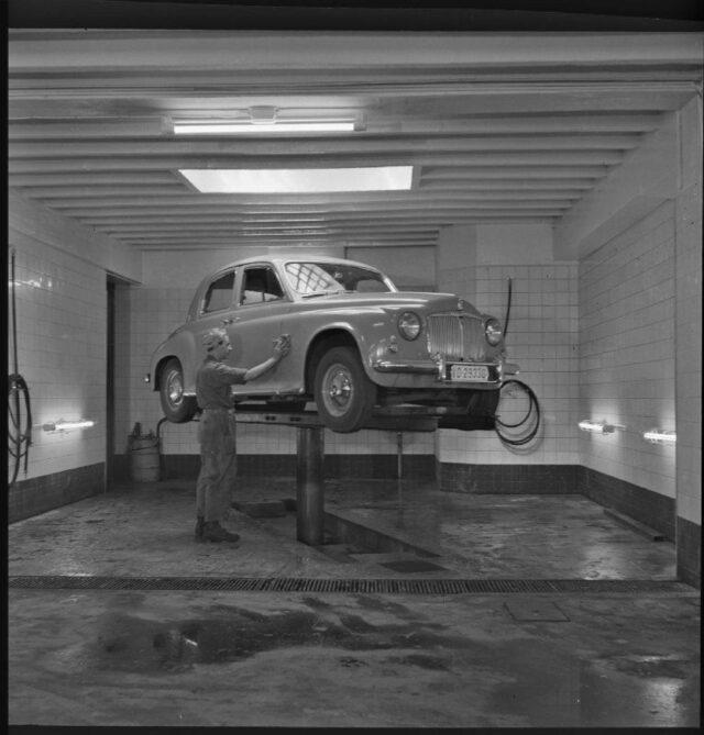 [Garage-Mitarbeiter mit Auto auf dem Autolift]