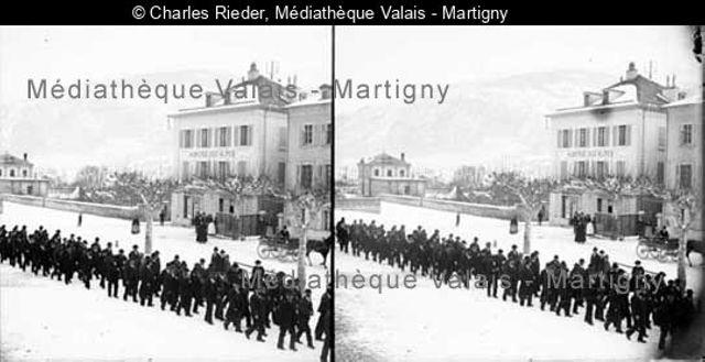 [Procession d'hommes devant l'auberge des Alpes, Sion]