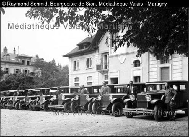 10 voitures FIAT avec leurs conducteurs alignés sur la place desvins Gay, Avenue de la Gare, Sion