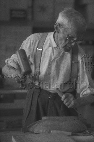 """""""Freizeitanlagen, Gemeinschaftszentren: Alter Mann am Schalen Schnitzen, FZA Bachwiesen, Zürich"""" - Älterer Mann mit Brille bei Holzarbeiten; um 1960"""