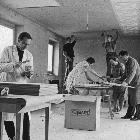 """""""Freizeitanlagen, Gemeinschaftszentren: Werkstatt FZA Bachwiesen, Zürich"""" - Männer und Frauen beim Sägen, Malen und Montieren von Deckenplatten; um 1970"""