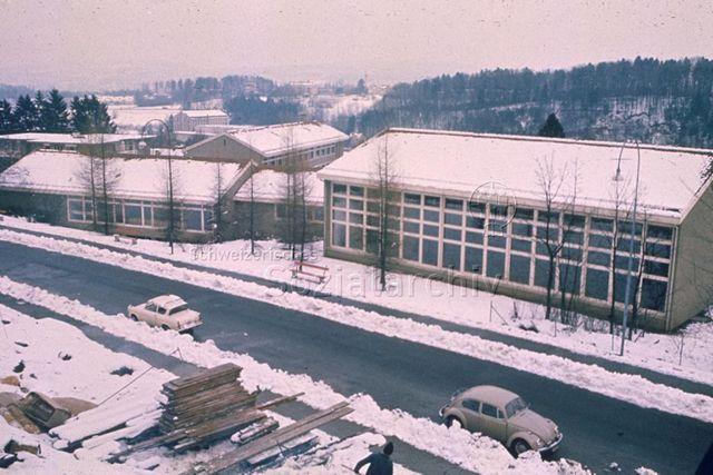 """""""Freizeitanlagen, Gemeinschaftszentren: Schulhaus und FZA Leimbach, Zürich"""" - Aussenansicht von Turnhalle und Freizeithaus im Winter; um 1960"""