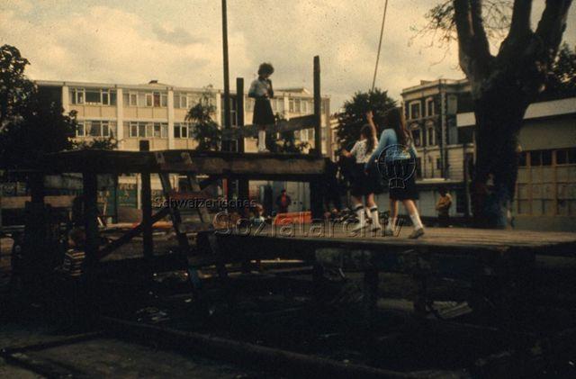 """""""Europäische Länder: Breakwell Art Center, Milton Keynes GB"""" - Mädchen spielen auf hölzernen Bühnen neben Bäumen, im Hintergrund sind Wohnblöcke zu sehen; um 1960"""
