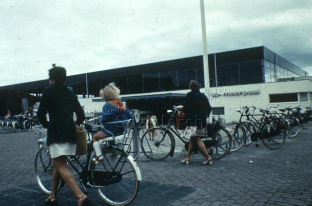 """""""Europäische Länder: De meer paal, Dronten Holland"""" - Frauen mit Fahrrädern, eine mit Kindersitz vor dem eckigen Gebäude mit Flachdach und grossen Fensterfronten; um 1970"""