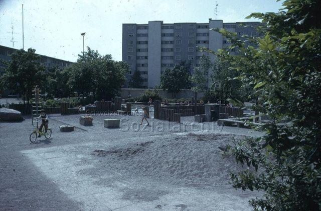 """Hirzenbach [Zürich], Sandspielplatz"" - spielende Kinder Kletterturm, Planschbecken; um 1975"