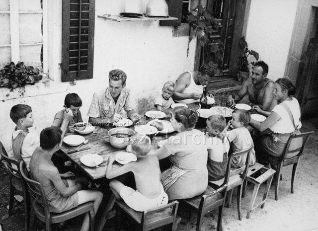 PraktikantInnenhilfe - Praktikant und zwei Familien sitzen am Tisch und essen; um 1965