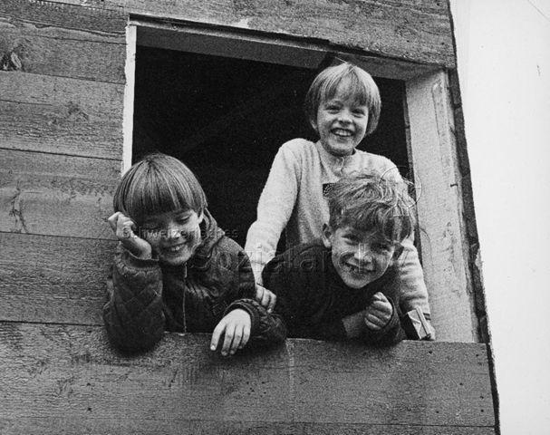 """Freizeitanlagen """"Bachwiesen"""", Zürich - Drei Kinder lachen aus dem Fenster einer Holzhütte in die Kamera; um 1970"""