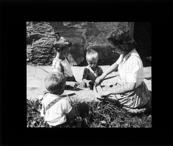 """Diaserie """"Reserve"""" und """"alte Dias""""; eine Frau und drei Jungen falten ein Papierboot; um 1950"""