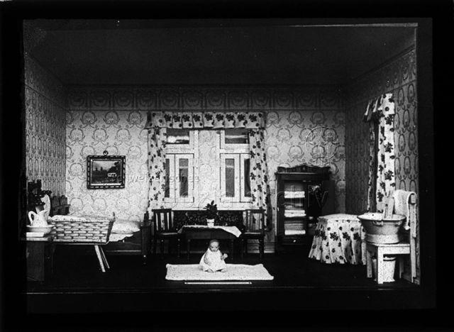 Diaserie zum Thema Säuglingspflege; ordentliches Schlafzimmer in einem Puppenhaus mit Säugling auf Teppich sitzend; um 1930