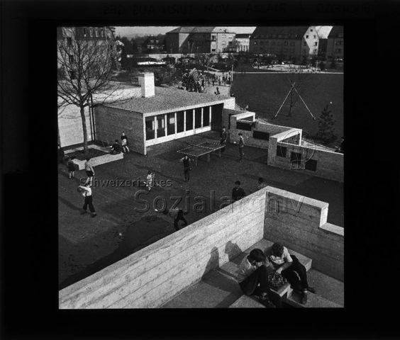 """Diaserie zu Spielplätzen in Zürich; Spielplatz Buchegg; """"Piazza vom Turm aus gesehen"""" - Platz mit diversen Spielmöglichkeiten; um 1960"""